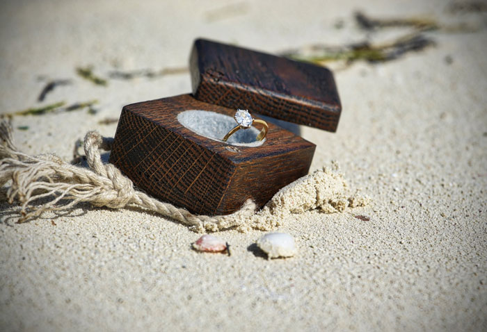 engagement ring in a box on the beach